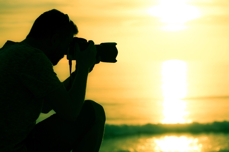 professional practice: Professional Photographer on Location Closeup. Sunset Photography. Stock Photo