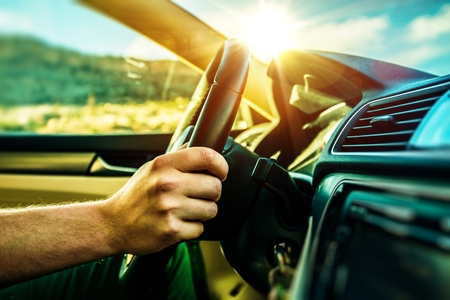 trips: Summer Time Car Trip. Car Traveling. Men Driving Down the Road During Scenic Sunset. Stock Photo
