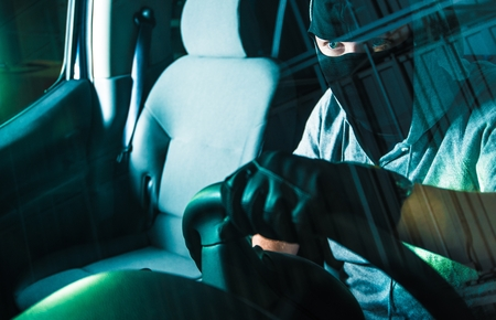 felon: Auto Theft Carjacking. Young Caucasian Male Carjacker in Black Mask Driving Stolen Car. Motor Vehicle Theft Concept Photography. Grand Auto Theft.