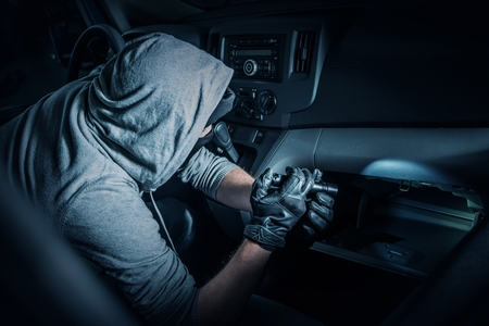 felony: Car Rubber in the Car. Rubber with Flashlight Looking for Valuable Items Inside the Car. Stock Photo