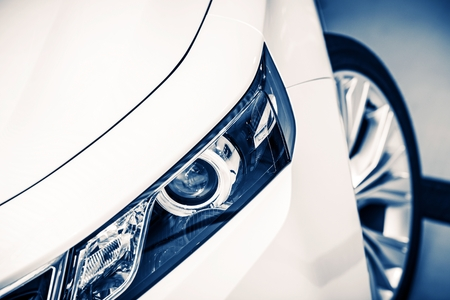 headlights: Modern Compact Car Headlight Closeup. Blue Color Grading. Stock Photo