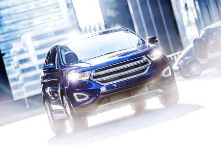 Modern Car on the City Street. Dark Blue SUV Sport Utility Vehicle. Transportation Theme. 新聞圖片