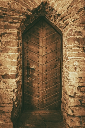 Vintage Wooden Castle Doors. Aged Stone Walls and the Medieval Wooden Door. Imagens