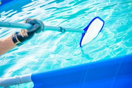 Backyard Garden Swimming Pool Cleaning Closeup. Taking Care of Pool. Stock Photo