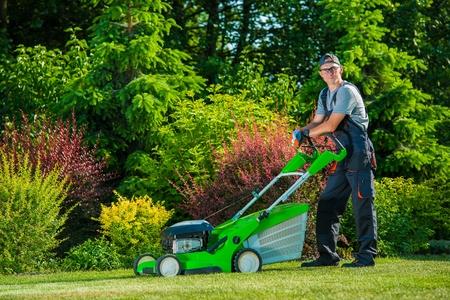 Glimlachend Professionele Tuinman met Zijn Benzine grasmaaier. Professionele Zomer Landscaping Works Stockfoto