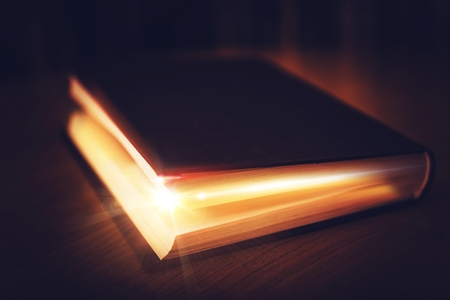 Book of Mysteries. Old Book with Glowing Content. Magical Book. Stock Photo