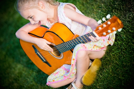 perform: Little Guitar Player. Seven Years Old Girl Playing Guitar and Singing Some Song.