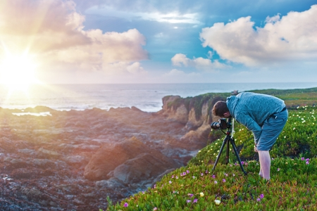 nature photography: Nature Photography. Photographer on the Ocean Cliff Taking Sunset Pictures.