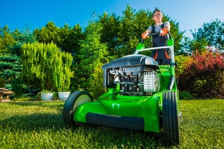 ビジネスの美化。庭師刈り取り裏庭の芝生。グリーン ガソリン芝刈り機 写真素材