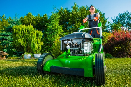 Landscaping Business. Gardener Mowing Backyard Lawn. Green Gasoline Lawn Mower