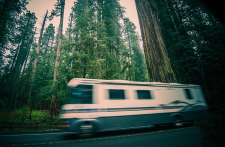 California RV Trip. Class A Recreational Vehicle Speeding on the Redwood Forest Road in Northern California, United States. Standard-Bild