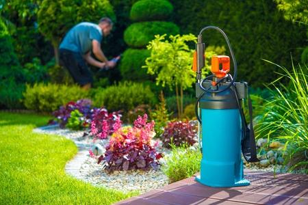 庭の害虫制御スプレーとバック グラウンドで男性の庭師。庭で農薬を散布します。ガーデニングのテーマです。
