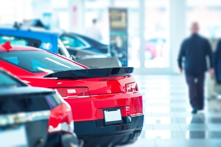 Buying Brand New Car in Local Car Dealership. New Cars Inside Exposition. American Car Dealer.