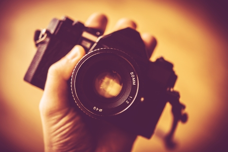 analog camera: Vintage Photography Concept. Vintage Analog Camera in a Hand. Stock Photo