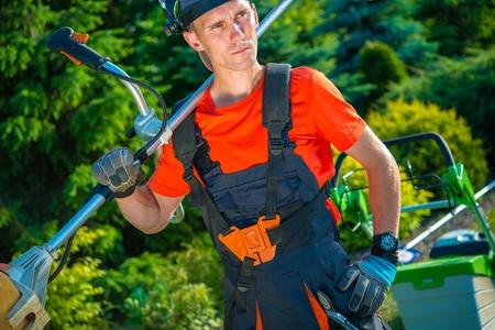jardineros: Satisfecho jardinero profesional con el cortac�spedes de c�sped del hombro. Paisaje de negocios. Foto de archivo