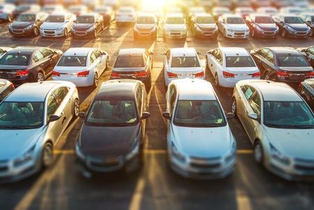 in row: Dealer Vehículos en Stock. Brand New Cars espera de los clientes sobre el distribuidor Parking Lot. Nueva sección Coches.