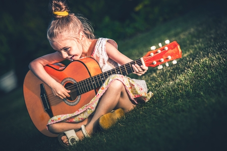 kids playing: Little Girl Playing Acoustic Guitar While Seating on the Backyard Grass.