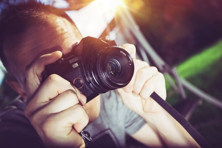 photographer: Caucasian Photographer with Vintage Analog Camera Taking Pictures.