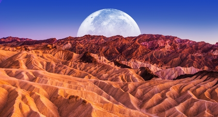 Death Valley National Park Badlands Sandstones Landscape and the Moon in California, United States.