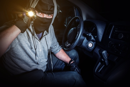 rubbery: Car Thief with Flashlight Inside Stolen Car at Night Stock Photo