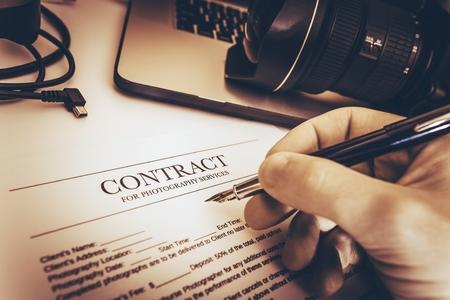 contratos: Fotografía de Contrato de Servicios Preparación de Fotógrafo Profesional en su escritorio de trabajo.