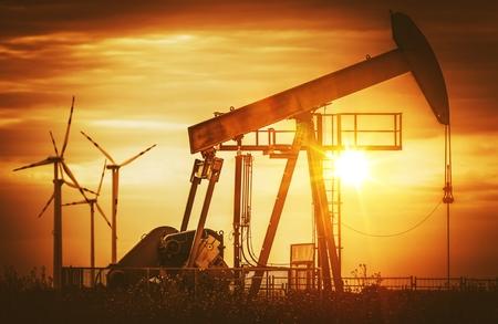 Erneuerbare Windenergie vs fossile Brennstoffe Konzept Fotografie. Old Fashioned Ölpumpe und Windkraftanlagen auf einem Horizont. Lizenzfreie Bilder