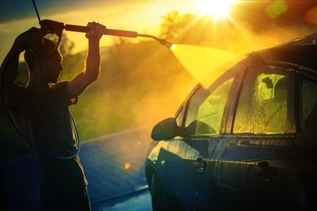 Voertuig wassen bij zonsondergang, hete zomermiddag Autowassen. Hogedruk water wassen.