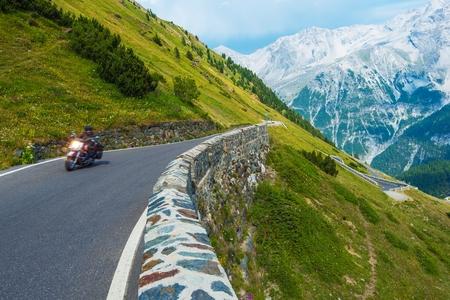 europe: Alpine Road Biker. Motorcycle on the Stelvio Pass, Italy, Europe. Scenic Italian Mountains Road. Stock Photo
