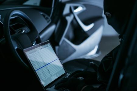 robo de autos: Hacker con el ordenador portátil en un coche por la noche. Hackear redes WiFi de la posición remota.