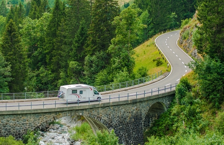 recreational: RV Camper Van Trip. Camper Van on the Mountain Road Bridge in Swiss Alps. Camper Traveling.