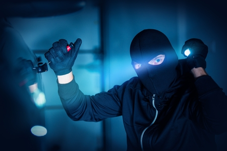 robo de autos: Car Thief Car Robbery Concept Photo. Caucasian Male Thief in Black Mask Trying to Open Car Using Custom Tool and Flashlight. Car Robber.