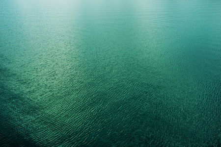Calm Clear Water Surface Photo Background. Green Lake Waters. Banco de Imagens