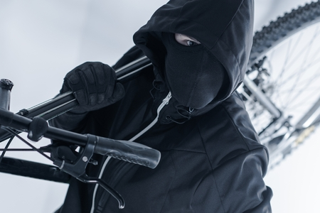 thieves: Bike Theft. Bike Thief in a Hood, Black Mask and Black Gloves. Caucasian Male Thief.