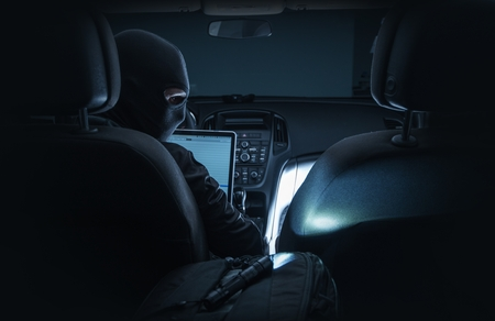 hackers: Hacking Car System. Car Hacker in Black Mask Hacking Vehicle Systems From Inside the Car Using Laptop Computer. Stock Photo