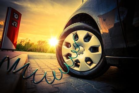 Tire Air vérification de la pression à la station de contrôle au coucher du soleil. Pomper de l'air dans le pneu.