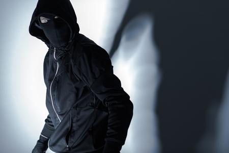 Caucasian Robber in Black Mask and Black Gloves Preparing for Robbery. Stockfoto