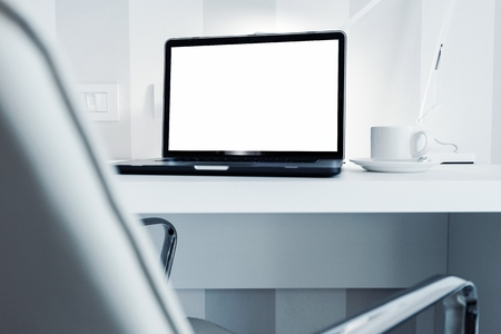office furniture: Modern Office Workstation with Laptop Computer. White Furnished Office Space.