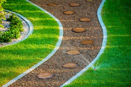 裏庭の芝生の自動スプリンクラー。裏庭に水をまきます。 写真素材 - 44872849
