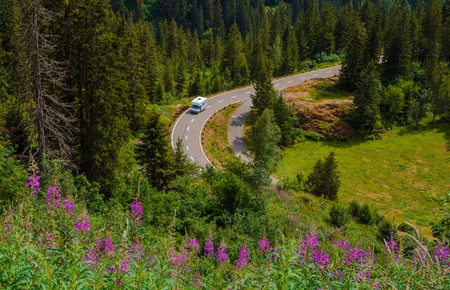 Camper Van Summer Travel. Rving Photo Theme. Small Class C Travel Camper on a Mountain Road During Summer Time.