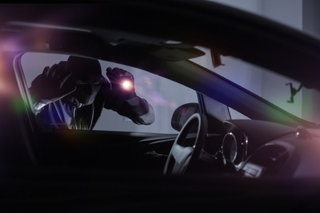thief: Car Robber with Flashlight Looking Inside the Car. Car Security Theme.