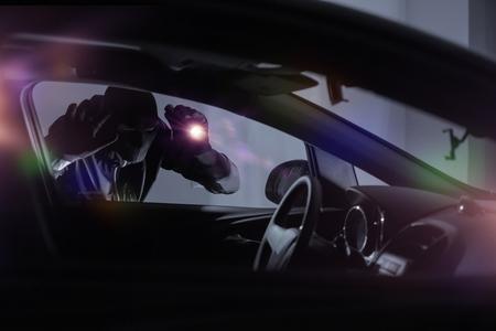 Złodziej samochodów z latarka Szukam wewnątrz samochodu. Temat bezpieczeństwa samochodów.
