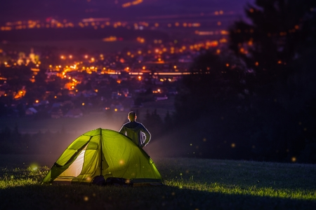 tent city: Countryside Camping with Scenic City View Down the Valley. Illuminated Cityscape at Night and the Camper with Illuminated Tent. Countryside Getaway.