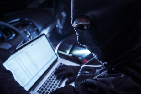 criminal: Hacker Inside the Car. Car Robber Hacking Vehicle From Inside Using His Laptop. Hacking On board Vehicle Computer.