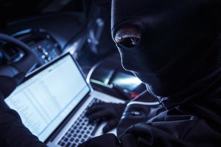 Hacker wewnątrz samochodu. Złodziej samochodów Hacking pojazdu od wewnątrz przy swoim laptopie. Hacking komputer pokładowy pojazdu. Zdjęcie Seryjne