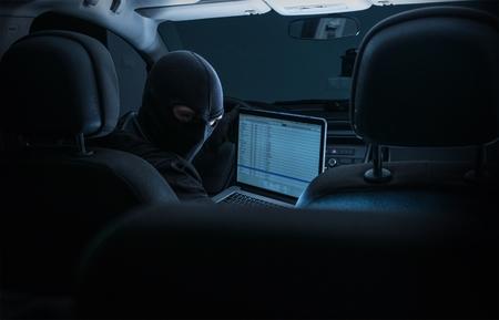 robo de autos: Hackear interiores Sistemas de coches. Ladrón de coches con Laptop intenta cortar Car System Modern Mientras asientos en el interior del coche. Foto de archivo