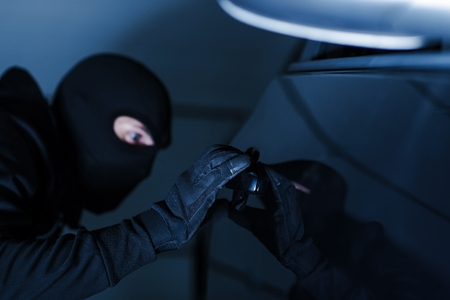 Motor Vehicle Theft Photo Concept. Car Theft in Black Gloves Stealing a Car.