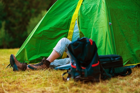 medium size: Resting Hiker in His Medium Size Tent. Wild Campsite. Hiking and Tent Camping Theme.