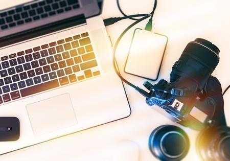 上からデジタル写真のワークステーション。現代のデジタル カメラ、レンズ、ノート パソコン。 写真素材