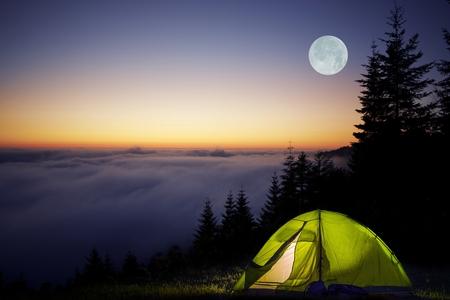 noche y luna: Tienda de campaña en un bosque durante la Noche de Luna Llena. Foggy montañas acampar. Foto de archivo