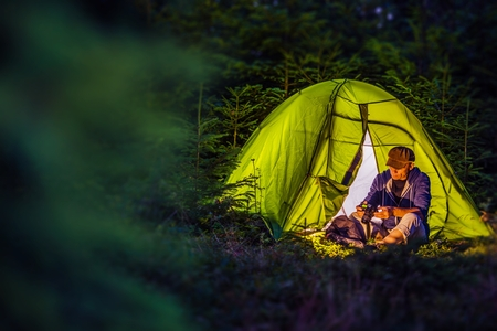 Overnight Forest Camping. Middle Age Caucasian Hiker with His Digital Camera and the Illuminated at Night Green Tent. Nighttime Mountains Hike and the Camping.